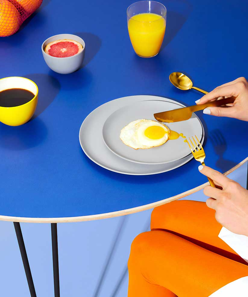 A cup of coffee and an egg with knife and fork