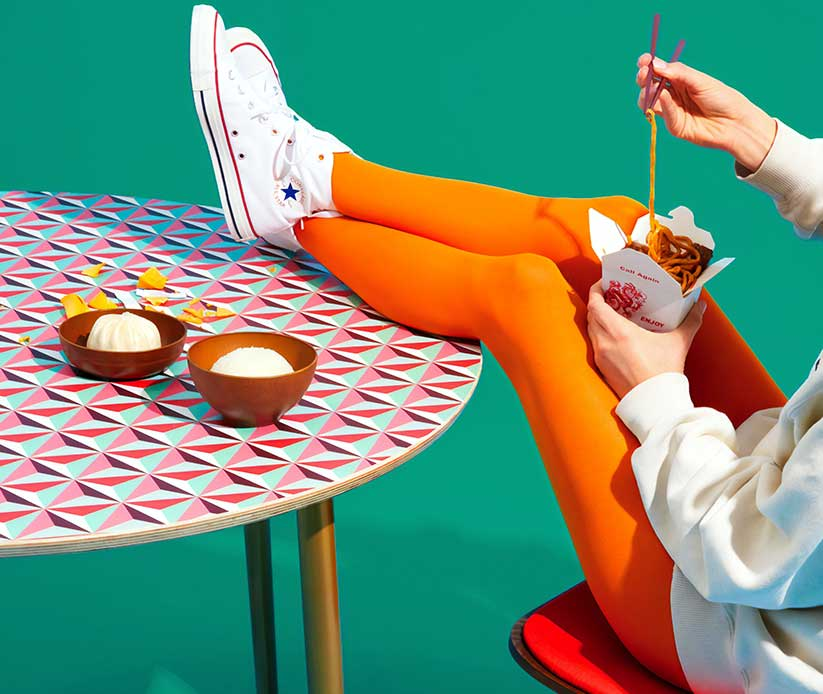 A girl with orange pants and white converse trainers with takeaway noodles