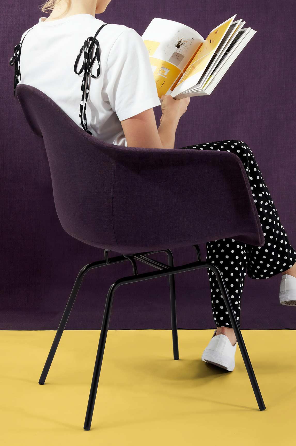 A girl facing towards a wall sat on a chair reading a book